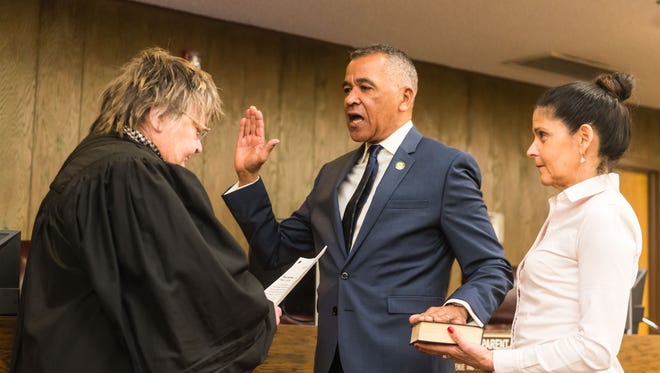 Millville City Commissioner Michael Santiago is sworn in to his second term by retired Superior Court Judge Georgia Curio on Tuesday night at City Hall during the governing body's reorganization meeting. His wife Lisa, president of the Board of Education, stands with him. Santiago was chosen to be mayor again later in the meeting.