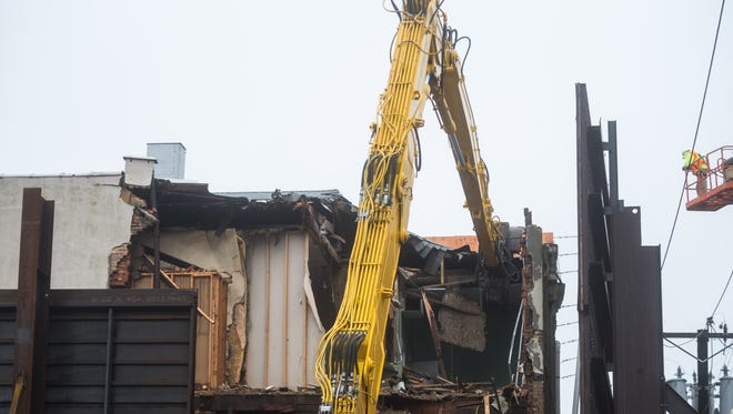 A crane begins the demolition of 109 E Main St in Millville on Wednesday, April 25.