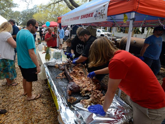 Members of Team Blowin' Smoke serve up BBQ during a previous Smokin' in the Square BBQ Cookoff in Seville Square. The event has moved this year to the Community Maritime Park and begins Friday.