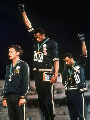 In this Oct. 16, 1968 file photo, extending gloved hands skyward in racial protest, U.S. athletes Tommie Smith, center, and John Carlos stare downward during the playing of the Star Spangled Banner after Smith received the gold and Carlos the bronze for the 200 meter run at the Summer Olympic Games in Mexico City. Australian silver medalist Peter Norman is at left.