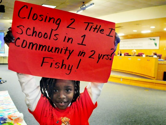 Kendra Jeanty, 6, of Titusville holds up a sign protesting