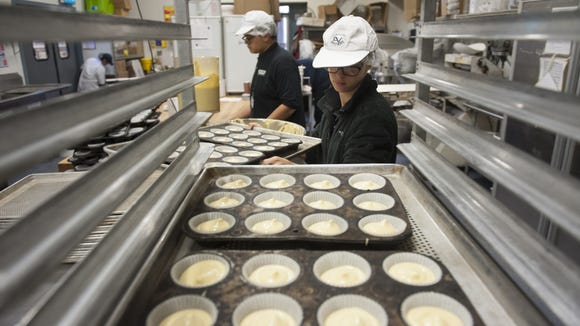 Brooke Creighton, 19, of Pitman, and Mathew Mazur, 19, of Clayton, both students from Bankbridge Development Center, fill trays of cupcakes at Liscio's Bakery in Glassboro while working as part of a workplace skills development program between the school and area businesses.