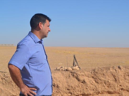 Yazidi journalist and soldier Sahar Attai  looks over