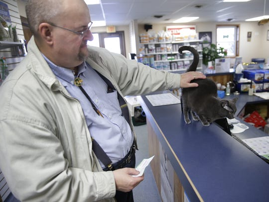 John Muller stops to pet resident clinic cat Birdie