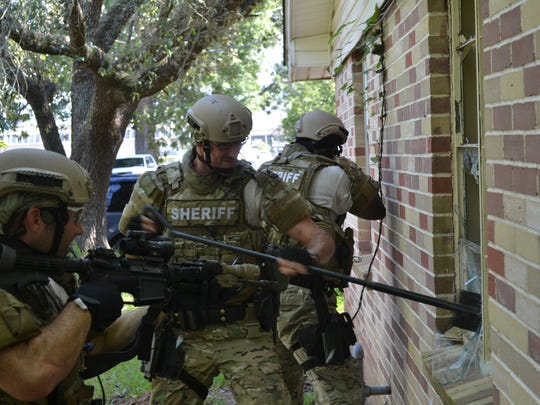 "Cpl. Michael Gill (center) performs a ""rake and break"" action in which he breaks out the glass of a window to gain access to a suspect. Cpl. Josh Daniels (left) sets his sights on the suspect inside while Sgt. Andre Clark (right) provides cover during a tactical training exercise Wednesday in Greenway Park."