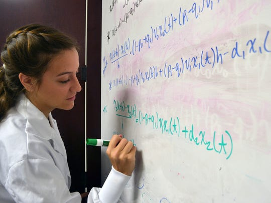 Hanna Dille, a junior math major at Anderson University, works Tuesday on an equation for her group's research on breast cancer cells.