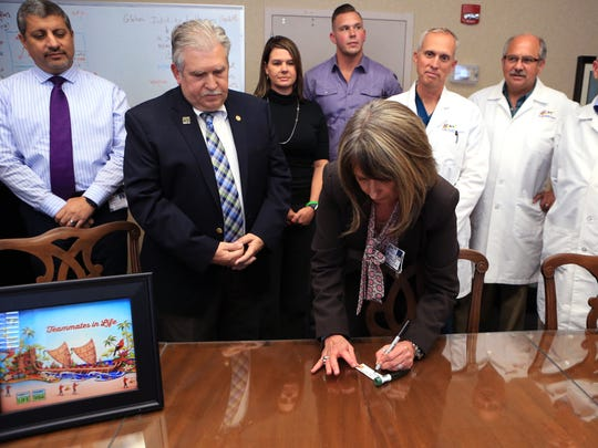 Karen Long, the vice president for patient care services at Driscoll Children's Hospital, signs a rose vial on Wednesday, Nov. 30, 2016. The vial will be added to the Donate Life Rose Parade float that will participate in the Rose Bowl Parade on Jan. 1, 2017.