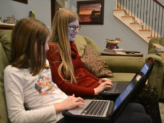 Zoe Willis, left, and her sister Kylie sit on the couch in their home in Anderson, checking their homework on Google Classroom.