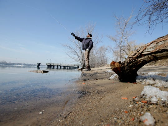 John Roseman, 42, of Farmington Hills casts his rod on the bank of the Detroit River at Belle Isle on Tuesday, March 21, 2017.