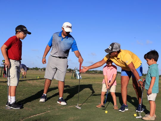 Marti Longoria-Potts works with Rickie Potts (from left), 13, Rieo Posada, 16, Roman Garza, 5, and Mason Garza, 3, at the  Tee2Green Golf Range and Teaching Facility on April 3, 2017. She recently won an award from the Southern Texas PGA for her work with young golfers.