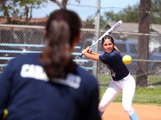 Carroll High School softball coach A.J. Caballero pitches to player Lisa Sosa in batting practice on Monday, April 25, 2017.
