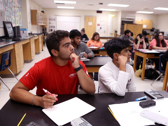 DJ Lopez, 16, and Trey Lira, 16, review practice questions in a physics class at Ray High School in May. DJ Lopez started working after his father was laid off and despite the fact that his father has found work again he continues to work.