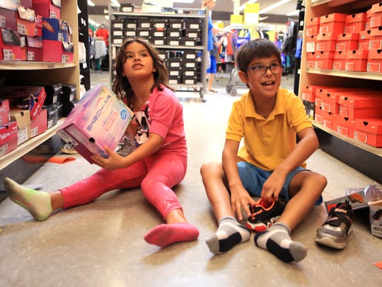 "Angeline Guerra, 7, and Daniel Guerra Jr,, 9, shop for new shoes during a back-to-school shopping event for children from the Boys and Girls Clubs of the Coastal Bend at Academy Sports + Outdoors on Thursday, Aug. 3, 2017. There were 30 children selected to spend $100 on back to school items paid for with gift cards donated by Academy. ""These shoes are just for showing off at school,"" Daniel said. His father, Daniel Guerra said the event is a blessing, especially for a single dad with two kids."