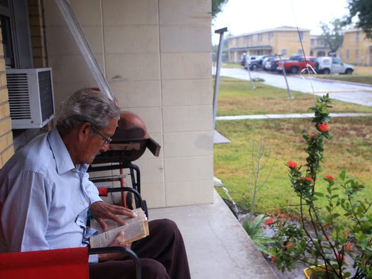 """Joe Matay reads the Bible as he sits on the front porch of his public housing complex at La Armada off Ayers Street in Corpus Christi on the afternoon before Hurricane Harvey made landfall. """"I'm not afraid,"""" he said as he pointed to the sky."""