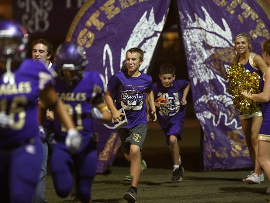 Children follow Sterling City football players out of their inflatable at the start of a game, Oct. 6, 2017, in Sterling City.
