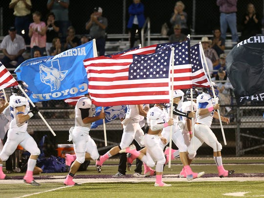 The Richland Springs Coyotes run onto the field waving the American flag and team flag before their game against the Sterling City Eagles on Oct. 6, 2017.