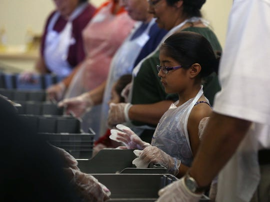 A young volunteer waits for a tray of meals to be loaded