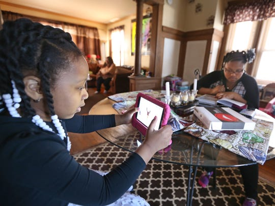 Giavanna McMillan, left, and sister MiÕAndrea McMillan, right, work on homework after getting home from school in their Rochester home Monday, March 26, 2018.