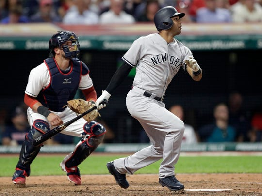 New York Yankees' Aaron Hicks watches his RBI double off Cleveland Indians starting pitcher Corey Kluber during the eighth inning of a baseball game, Thursday, July 12, 2018, in Cleveland. Indians catcher Yan Gomes watches.