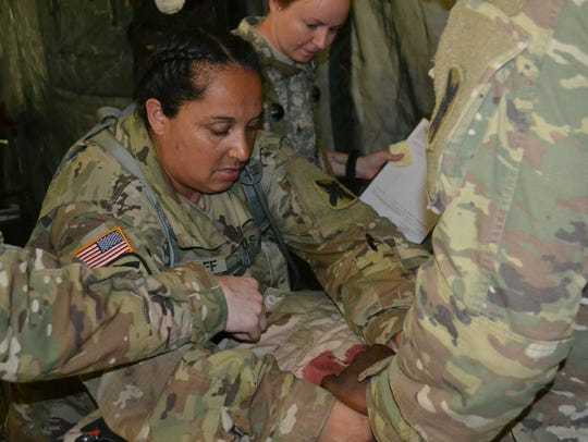 Sergeant First Class Karen Gangloff of Lafayette treats