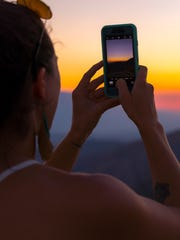 A Joshua Tree National Park visitor takes a photo of the sunset at Key's View.
