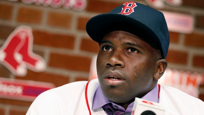 Rusney Castillo talks with reporters following a baseball game between the Boston Red Sox and the Seattle Mariners in Boston, Saturday, Aug. 23, 2014. The Red Sox announced during the game that they signed Castillo, a Cuban defector, to a seven-year contract, beginning in 2014.