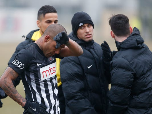 Partizan Belgrade's Brazilian player Everton Luiz, left, leaves the field during a Serbian championship match between Rad and Partizan, in Belgrade, Serbia, Sunday, Feb. 19, 2017.  Luiz was in tears after suffering persistent racist chants during his team's 1-0 victory against Rad in the Serbian premiership. The Brazilian, who joined Partizan from the Swiss league in 2016, received monkey chants and other abuse, including a racist banner on the stands where Rad fans were standing. (AP Photo/Miroslav Todorovic)