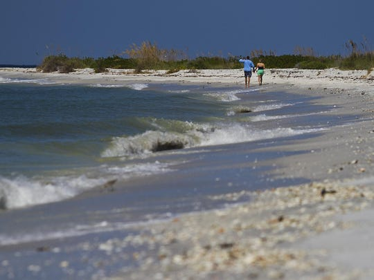 A couple walks along the beach shore to Cayo Costa State Park during a recent trip to the island.