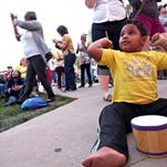 Maddox Schwalm-Bell, 4, of Iowa City, jams on a tiny drum while watching a percussionist on stage during Sierra Leone's Refugee All-Stars set at the Iowa Soul Festival in 2014.