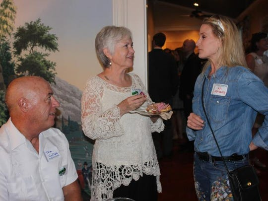 Tom Cullen and Wray Estes, center, talk with A.D. Maddox, the featured artist for River Swing.