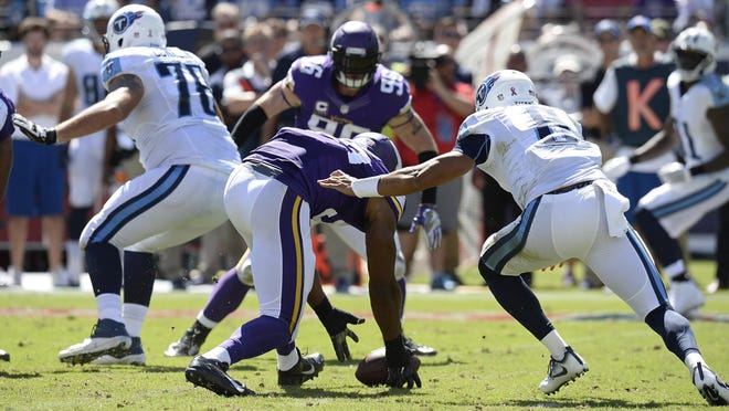 Minnesota Vikings defensive end Danielle Hunter, center, recovers a fumble by Tennessee Titans quarterback Marcus Mariota (8) and returns it 24 yards for a touchdown in the second half of an NFL football game Sunday, Sept. 11, 2016, in Nashville, Tenn.