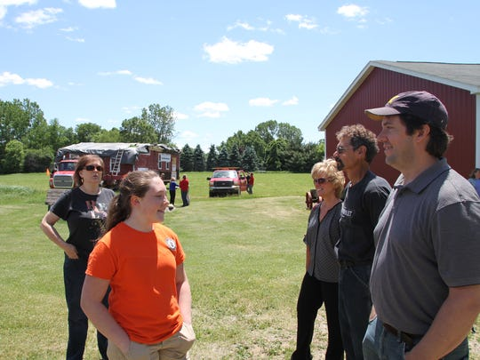 Members of the Warner and Bennett family celebrate the arrival of the Hicks one-room schoolhouse, which sits on a flat-bed truck behind them. From left to right are:  Donna Warner, Anna Bennett, Laura Warner, Elroy Warner and Tim Bennett.