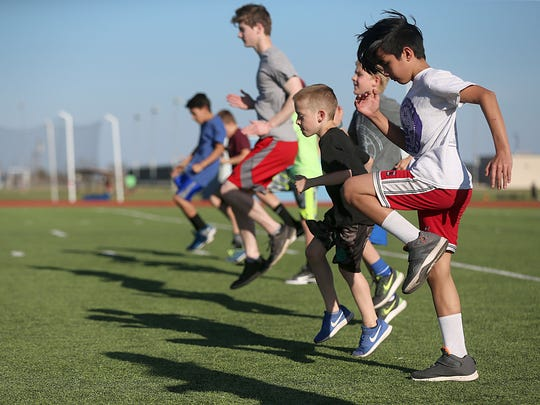 Home-schoolers participate in warm-ups before track practice at Lake View High School's field March 22, 2018.