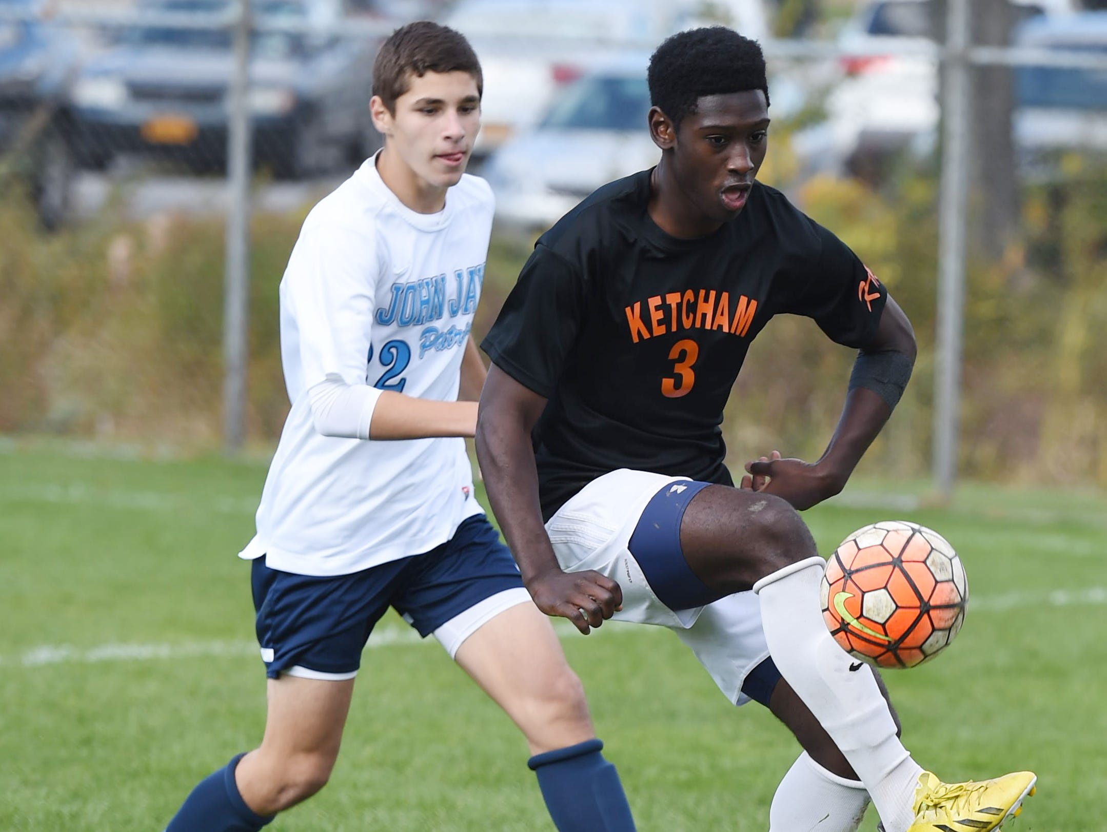 Ketcham's Eddie Armah gets the ball under control as John Jay's Michael Fino moves in on him during Saturday's game in Wappingers Falls.