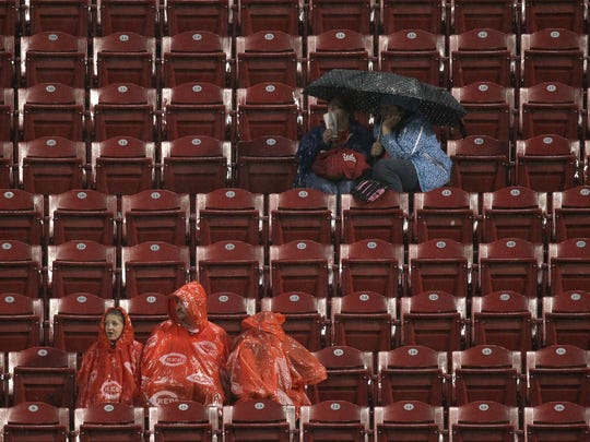 Reds fans take cover from the rain Wednesday as the