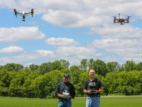Chris Knight, CEO of SparkNET, and Bill Bongle, a retired police officer and founder of the Green Bay Area Drone User Group, fly drones at Southwest Park in De Pere.