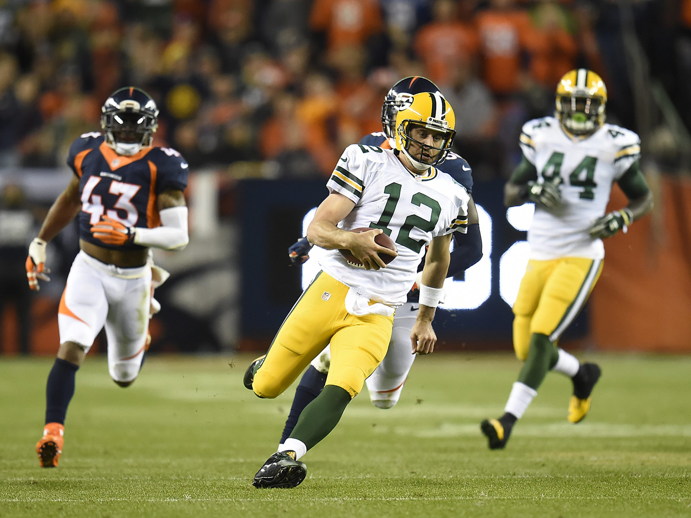 Green Bay Packers quarterback Aaron Rodgers (12) runs with the ball against the Denver Broncos during Sunday night's game at Sports Authority Field in Denver, Colo. Photo by Evan Siegle/P-G Media