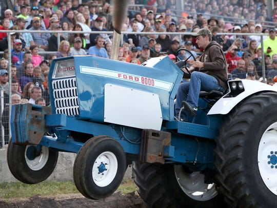 A tractor's front wheels leave the ground under strain