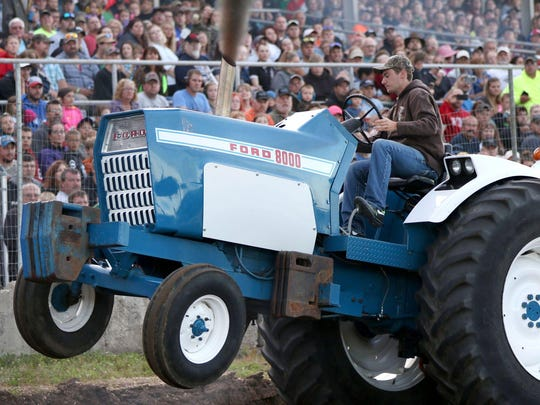 A tractor's front wheels leave the ground under strain on July 8 during the Marshfield Parish Truck and Tractor Pull at the Marshfield Fairgrounds.