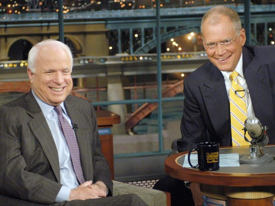 "Sen. John McCain and ""Late Show"" host David Letterman watch the monitor that is showing McCain's family members waiting in the green room during the taping of the ""Late Show with David Letterman"" on Sept. 1, 2004, in New York City."