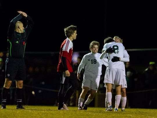 Matt Lukasik (18) celebrates with his teammates after a goal against Stevens Point Area Senior High.