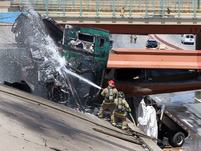 Firefighters cool the engine and fuel tanks on a tractor-trailer