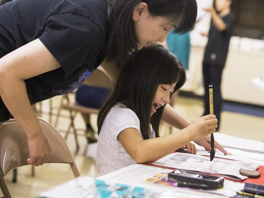 Kaho Tsuzuki practices Japanese calligraphy during Japanese Cultural Camp on Tuesday at Second Missionary Baptist Church.