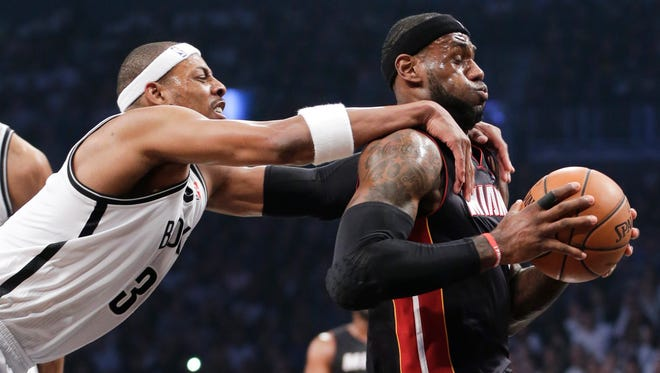 Brooklyn's Paul Pierce, left, fouls Miami Heat's LeBron James as he drives through the lane to score in the first quarter during Game 3 of an Eastern Conference semifinal playoff game on Saturday in New York. Pierce was called for a flagrant foul and James scored on the play.