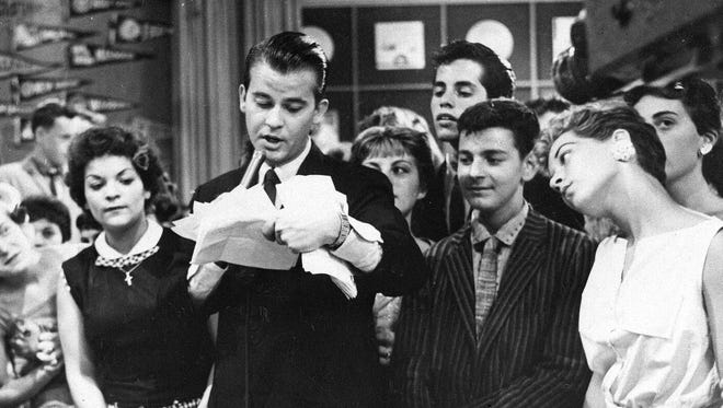 "Dick Clark is seen surrounded by fans during a 1957 television broadcast of ""American Bandstand."""