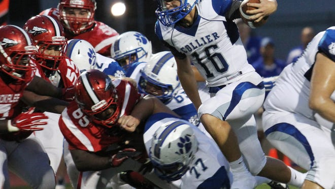 Barron Collier's Jack Bueltel leaps through a hole in Immokalee's defense during a game in Immokalee on Friday night.