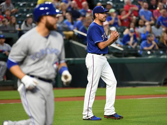 Texas Rangers starting pitcher Matt Moore walks back to the mound after hitting Toronto Blue Jays' Russell Martin, foreground, with a pitch during the first inning of a baseball game Friday, April 6, 2018, in Arlington, Texas. (AP Photo/Jeffrey McWhorter)