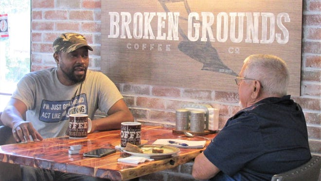 Herschell Hargrave, who owns Broken Grounds Coffee with his wife, Charity, has a cup of coffee with customer and new friend Dan Hostetler on Friday.