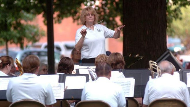 Christie Cochran directs the Coshocton Community Band during a previous concert on the court square in this Tribune file photo.
