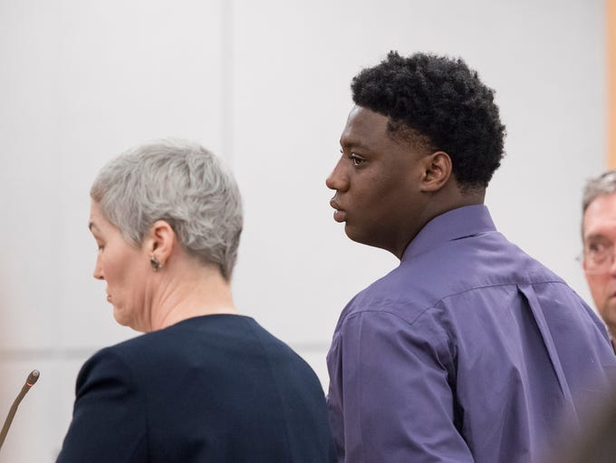 Jordan Dumas, right, listens to testimony during his